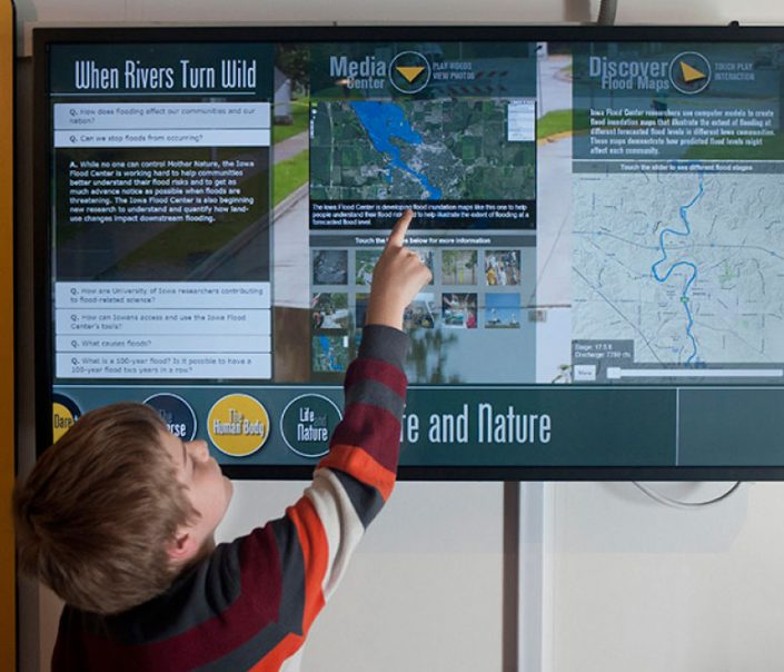 A young boy points at a computer screen showing IFC tools and resources in the UI Mobile Museum