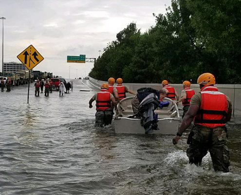 Rescue personnel wade through floodwater on a Houston freeway to help stranded motorists.