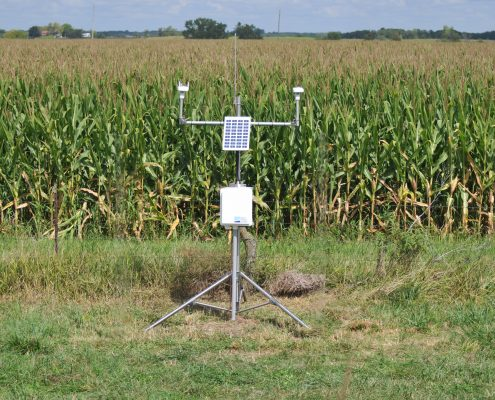 A tripod with numerous weather instruments stands next to an Iowa cornfield.