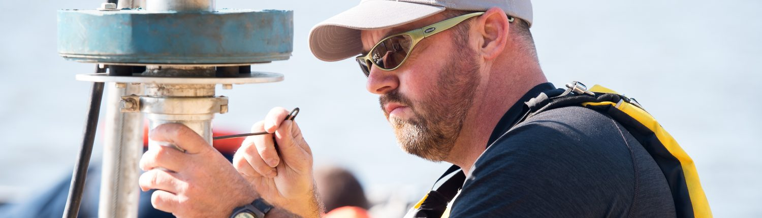 A researcher adjust equipment while conducting fieldwork on a boat.