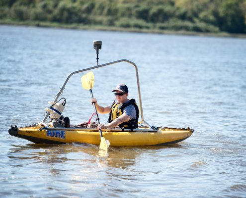 An IFC researcher in a kayak collects bathymetric data.