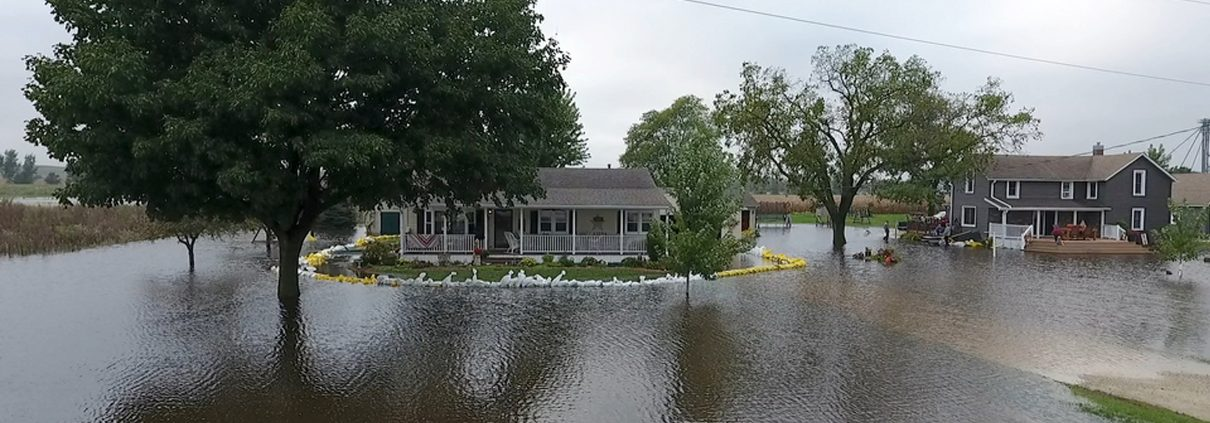 Sandbags protect a house that is an island in a sea of floodwater.