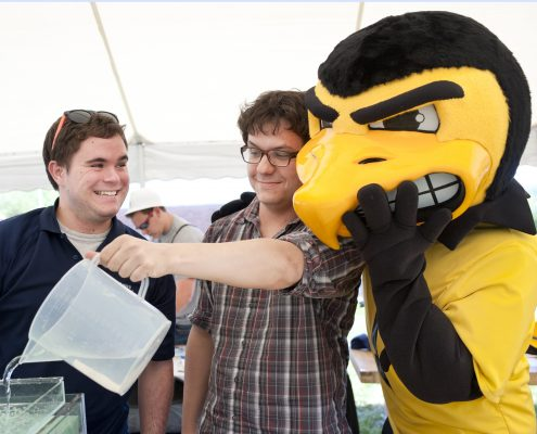 UI mascot Herky gets up close and personal with two IFC researchers at a STEM festival for K-12 students.