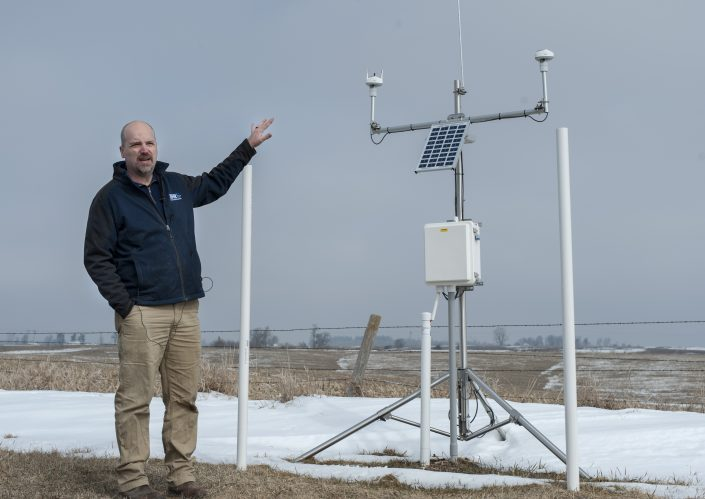 IFC researcher Jim Niemeier stands next to one of the IFC hydrologic stations deployed in a farm field.