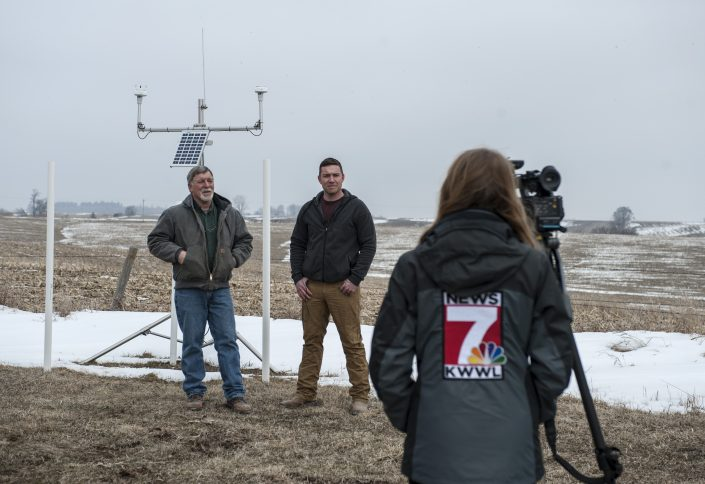 Farmer Stewart Maas and his son Jared stand next to the IFC hydrologic station deployed on their farm while a TV news camera person films the event.