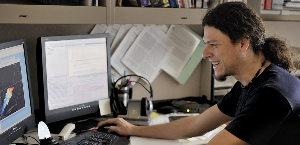 Iowa Flood Center researcher Ricardo Mantilla smiles as he works at his computer.