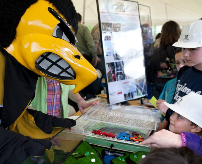 The University of Iowa mascot, Herky, visits with kids at at STEM festival where they are learning about watersheds.