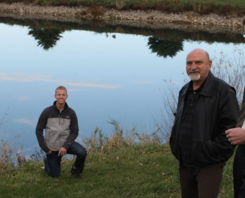 Larry Weber and members of his team near an Iowa farm pond.