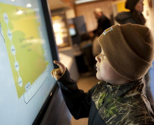 A young boy in a stocking hat tries out the IFC interactive display in the UI Mobile Museum.