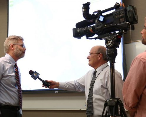 IFC Associate Director Nate Young is interviewed by a television news reporter on camera.