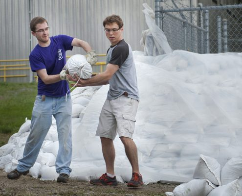 Two students fill and pile sandbags during 2008 flooding on the University of Iowa campus.