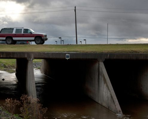 A three-box culvert with a sensor attached and a pickup driving overhead.