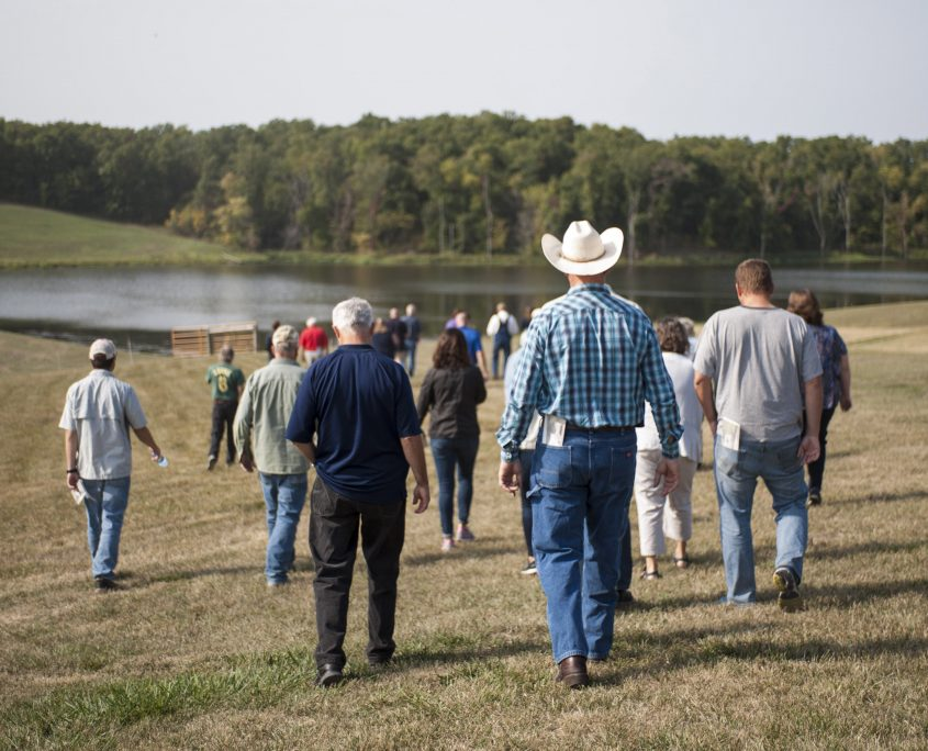 A group of people walks away from the camera toward a beautiful farm pond.