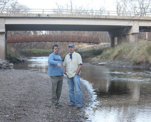 IFC researchers James Niemeier and Anton Kruger stand in front of a bridge with one of the sensors attahed