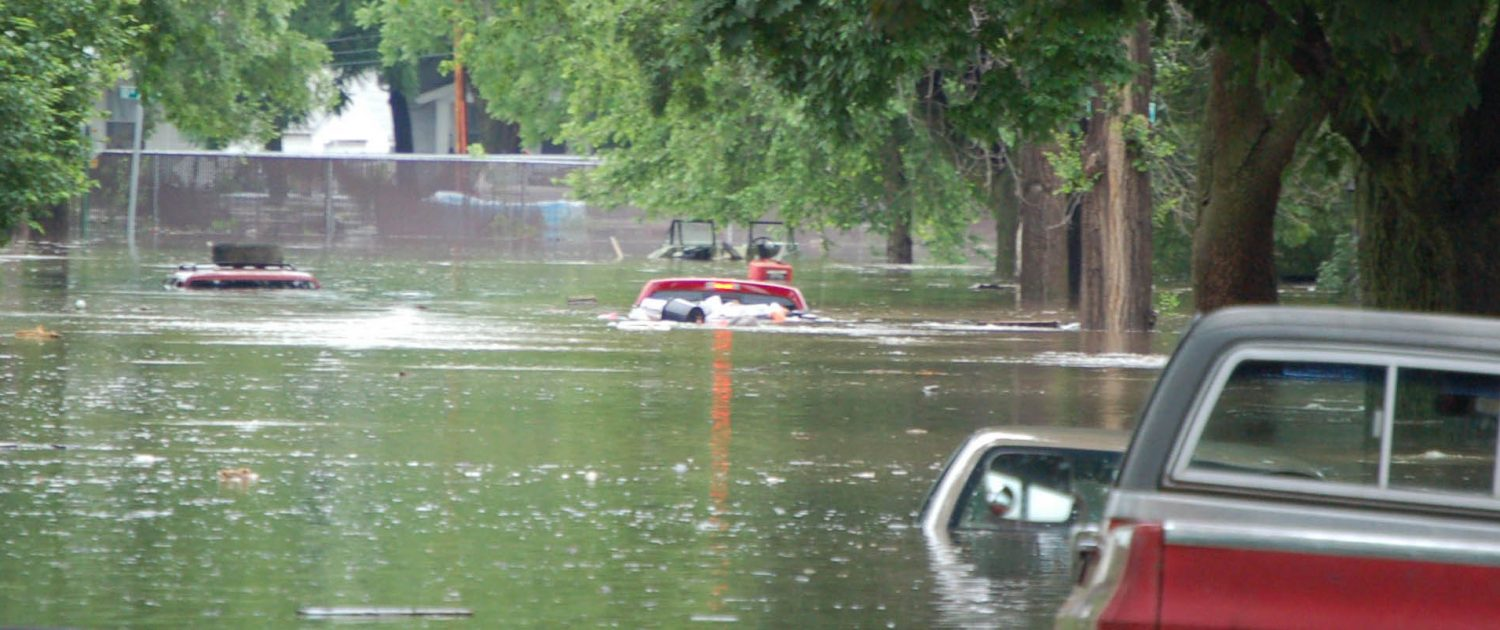 A flooded Cedar Rapids street with an inundated pickup truck in the foreground