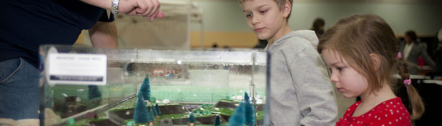 A young boy and girl watch as an IFC grad student demonstrates how water moves through a watershed using the IFC's floodplain model.