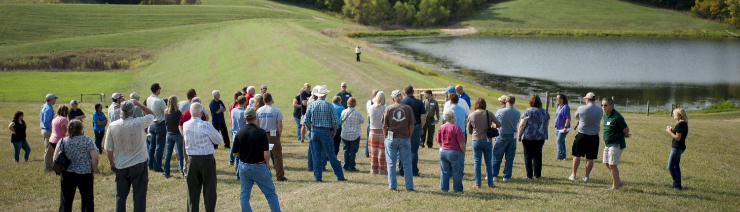 A large group of people look at a farm pond in the Soap Creek Watershed in southeast Iowa