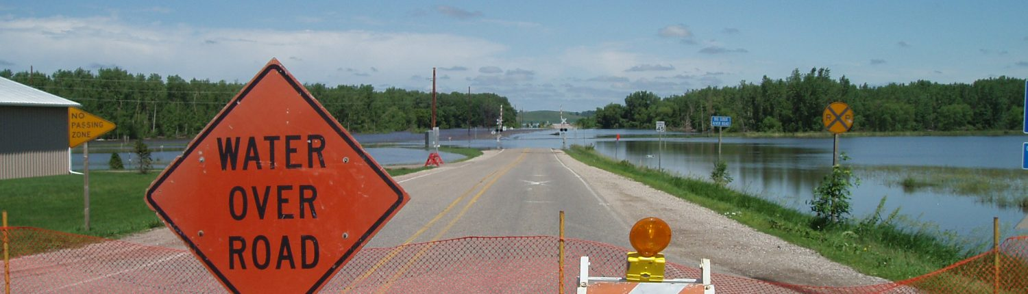 "Flooded roadway in rural Iowa, with an orange hazard sign that says ""Water Over Road"""