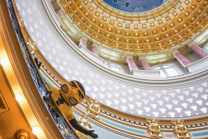 Herky the Hawkeye leans over an ornate gold railing with the interior of the capitol dome above him.