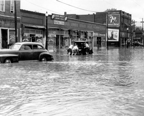 A black and white photo of cars in a flood