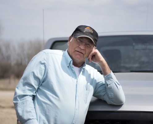 A man in a hat leans against a pickup truck.