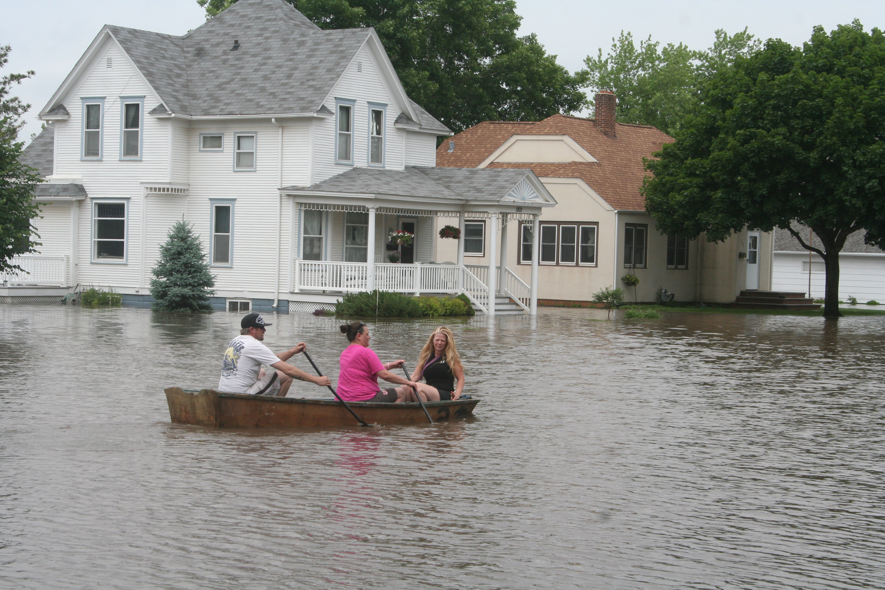 Three people in a boat paddle down a street-turned-river in Rock Valley, Iowa.