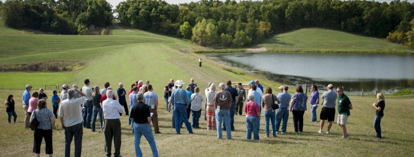 People Look at a Pond as part of a tour of the Soap Creek WAtershed.