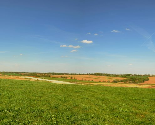 A panoramic view of a green field and blue sky, with three white radar units.
