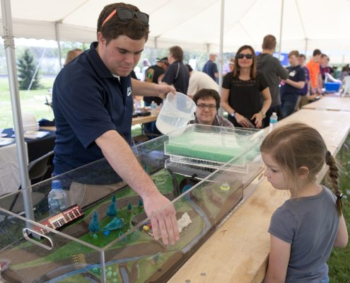 A little girl looks on as an IFC graduate student demonstrates the watershed model.