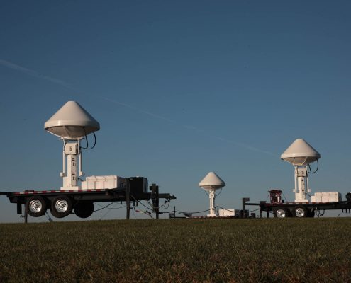 Three radars in a field against the backdrop of a blue sky.