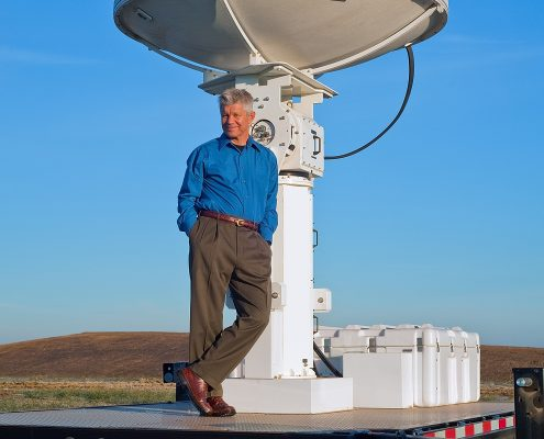 A man leans against a radar in a field.