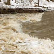 Raging brown water flows by streambanks covered with snow.