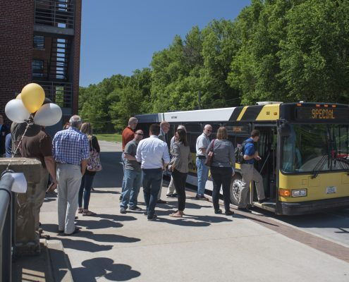 Guests board the bus in front of the Stanley Hydraulics Lab