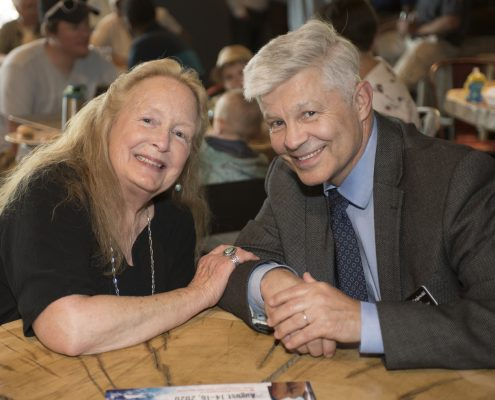 Witold Krajewski and a woman pose for a photo at a table