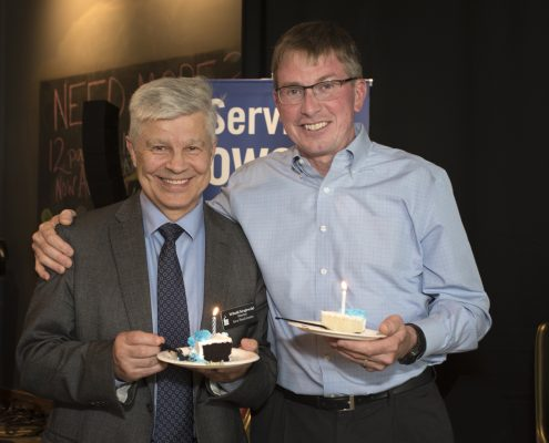 Larry and Witold hold cake and smile in front of a poster