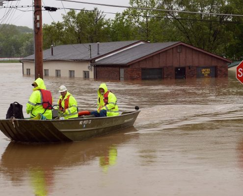A group of people float down a flooded road